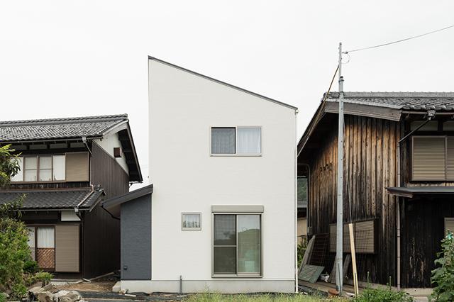 古い街並みに立つ白い家